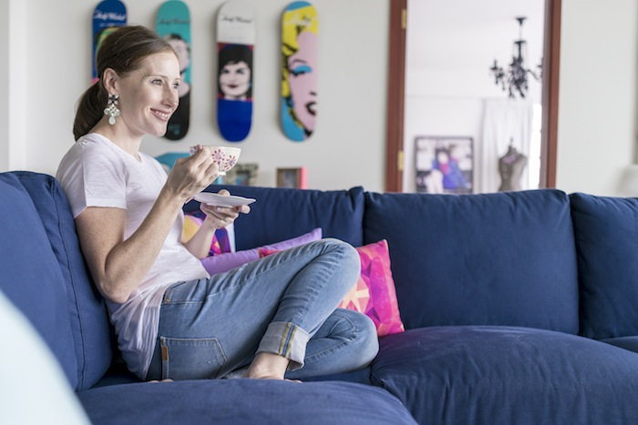 maura thompson sitting on her blue sofa