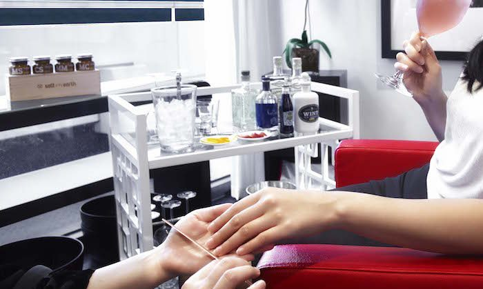 woman drinking gin and having her nails done